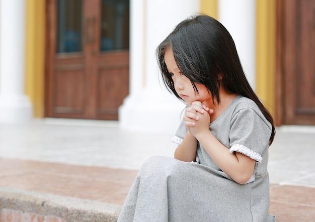 Kleines asiatisches mädchen, das an der kirche sitzt und betet Premium Fotos