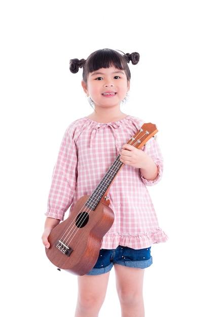 Kleines asiatisches mädchen, das ukulele und lächeln über weißem hintergrund hält Premium Fotos