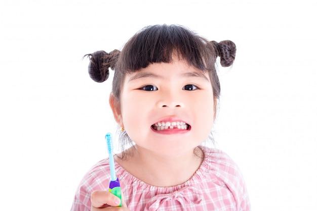 Kleines asiatisches mädchen, das zahnbürste und lächeln über weißem hintergrund hält Premium Fotos