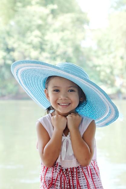 Kleines asiatisches mädchen draußen im sommerhut Premium Fotos