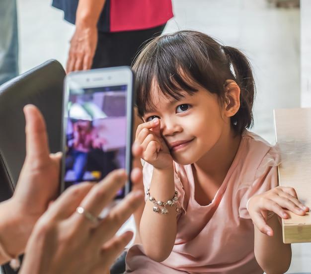 Kleines asiatisches mädchen machen ein foto mit einem smartphone. Premium Fotos