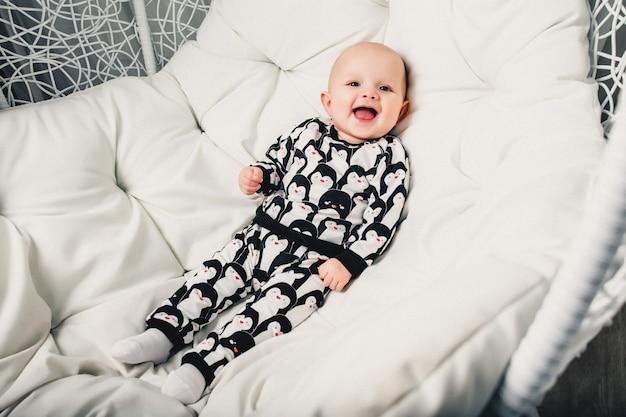 Kleines baby, das auf einem runden schwingen und einem lächeln liegt Premium Fotos