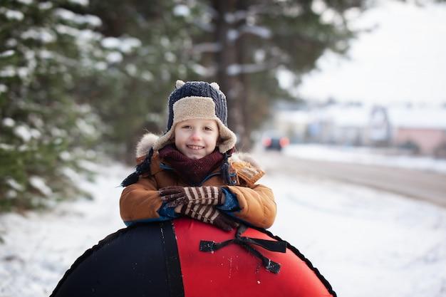 Kleines baby des porträts mit rohr am wintertag. nettes jungenspiel draußen im schnee. Premium Fotos