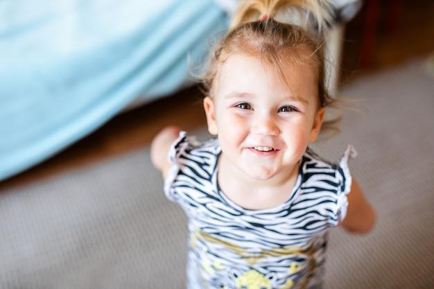 Kleines baby im weißen t-shirt mit spielwaren auf dem boden zu hause Premium Fotos