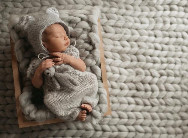Kleines baby in der grauen kleidung schläft auf woolen decke Kostenlose Fotos