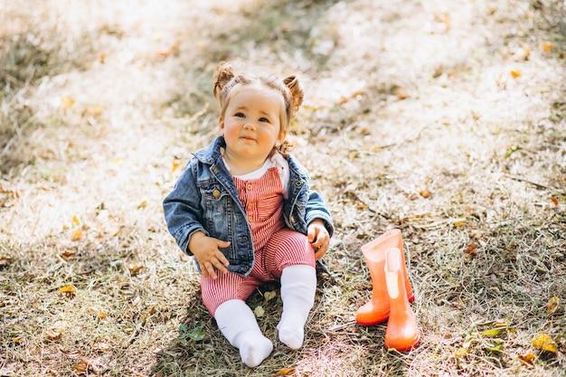 Kleines baby mit den regenstiefeln, die im park sitzen Kostenlose Fotos