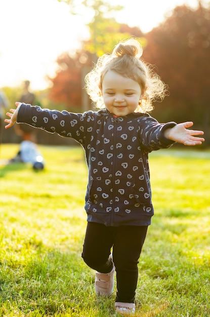 Kleines baby spielt im park in der hintergrundbeleuchtung. Premium Fotos