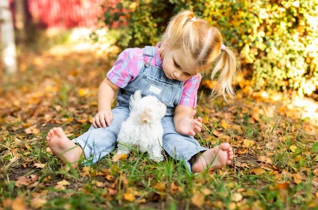 Kleines blondes kleinkindmädchen mit zwei borten, die mit nettem weißem welpen spielen Premium Fotos