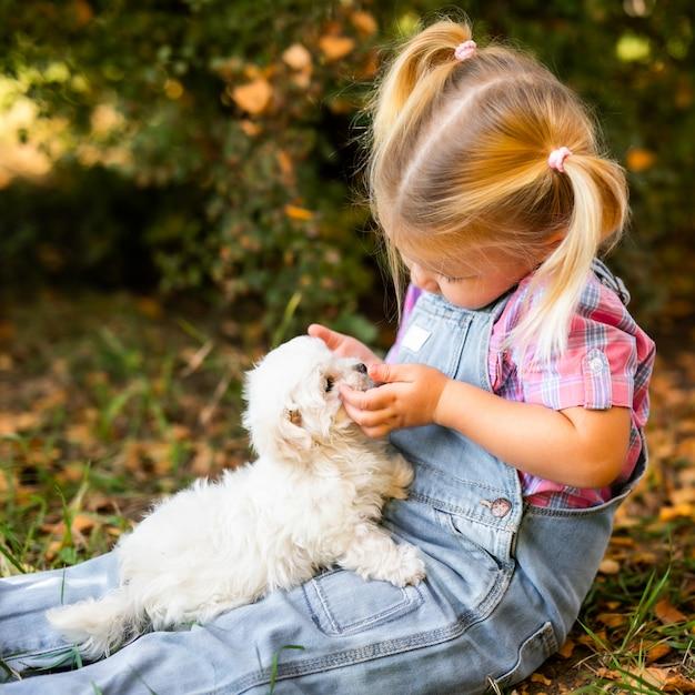 Kleines blondes kleinkindmädchen mit zwei zöpfen, die mit netten weißen welpen spielen Premium Fotos
