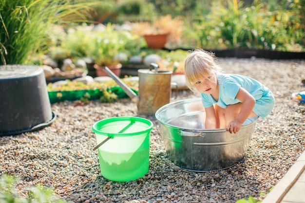 Kleines blondes mädchen, das am garten mit wasser in einem zinnbecken spielt. Premium Fotos