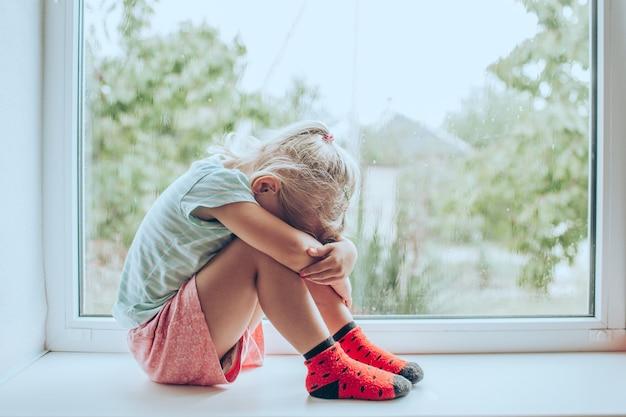 Kleines blondes mädchen, das auf dem boden sitzt und ihre knie umarmt, in der nähe des fensters zu hause, den kopf gesenkt, gelangweilt, mit den kämpfen der eltern beunruhigt Premium Fotos