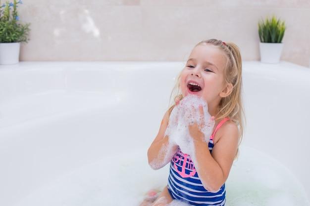 Kleines blondes mädchen, das schaumbad im schönen badezimmer nimmt kinderhygiene. shampoo, haarbehandlung und seife für kinder. kind, das in der großen wanne badet. Premium Fotos