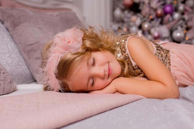 Kleines blondes mädchen im bett neben weihnachtsbaum. heiligabend Premium Fotos