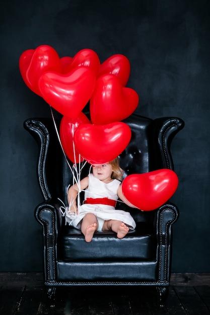 Kleines blondes mädchen im weißen kleid mit dem roten band, das auf dem lehnsessel mit rotem herzballon am valentinstag sitzt Premium Fotos