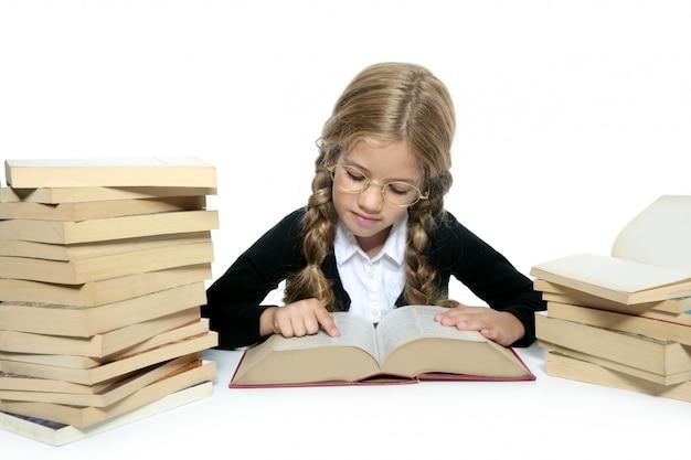 Kleines blondes studentenschulemädchen, das altes buch liest Premium Fotos