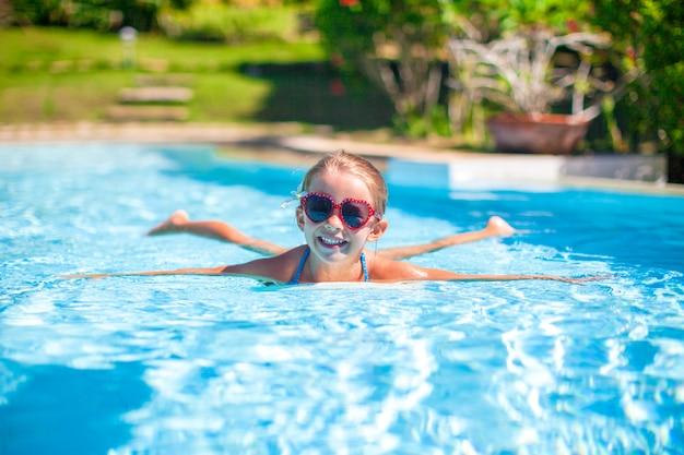 Kleines entzückendes glückliches mädchen schwimmt im swimmingpool Premium Fotos