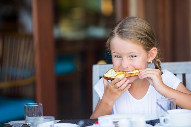 Kleines entzückendes mädchen, das brot mit butter und honig auf frühstück isst Premium Fotos