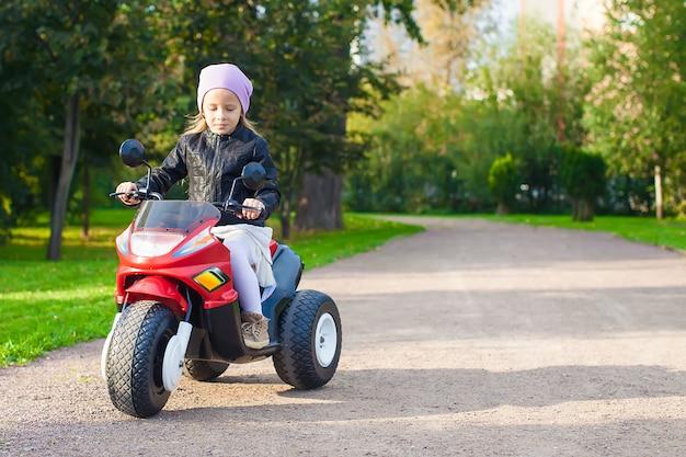 Kleines entzückendes mädchen, das spaß auf ihrem spielzeugmotorrad hat Premium Fotos