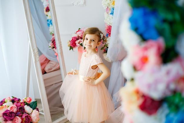 Kleines entzückendes mädchen im kleid, das weg im raum aufwirft und schaut, füllte mit blumen. Premium Fotos