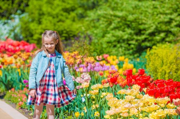 Kleines entzückendes mädchen in blühendem tulpengarten Premium Fotos