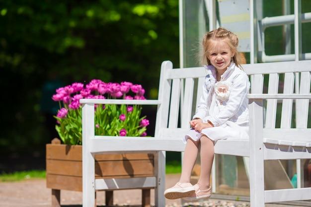 Kleines entzückendes mädchen mit blumen im tulpengarten Premium Fotos