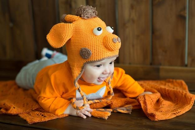 Kleines europäisches baby in leuchtend orangefarbenen kleidern Premium Fotos