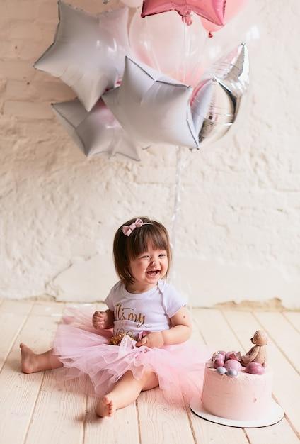 Kleines geburtstagskind. bezauberndes baby im rosafarbenen kleid sitzt auf dem stuhl Kostenlose Fotos