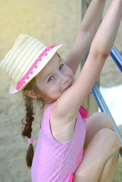 Kleines gir im strohhut, der am spielplatz spielt. Premium Fotos