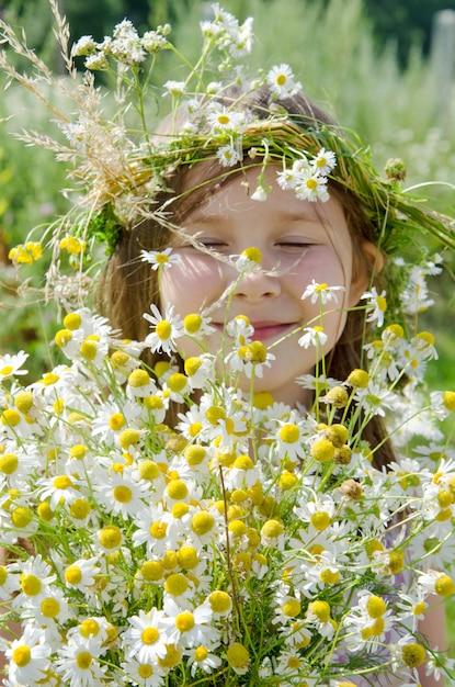 Kleines glückliches mädchen in einer girlande von feldblumen auf der wiese Premium Fotos