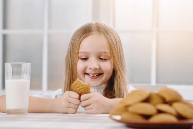 Kleines hübsches mädchen lächelt, während es süßen keks isst Premium Fotos