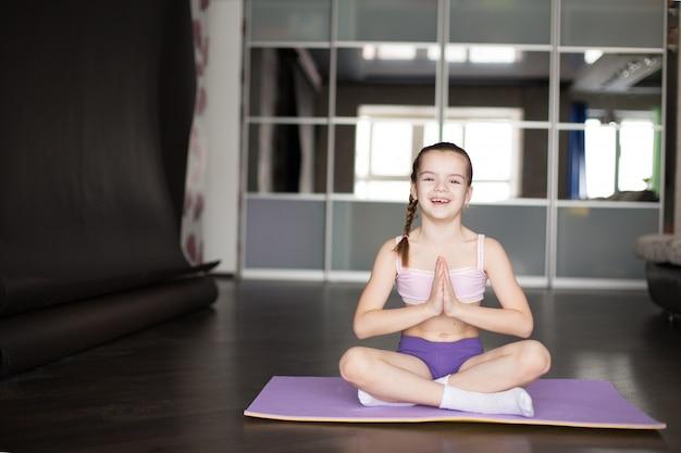 Kleines kaukasisches auf matte in der yogahaltung sitzendes und meditierendes mädchen. Premium Fotos