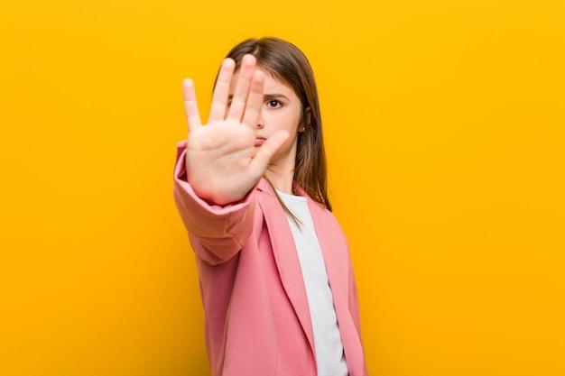 Kleines kaukasisches nettes mädchen, das mit der ausgestreckten hand zeigt das stoppschild, sie verhindernd steht. Premium Fotos
