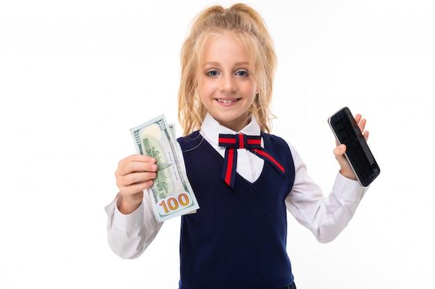 Kleines kaukasisches schulmädchen mit blonden haaren kaufen ein telefon und behält geld Premium Fotos