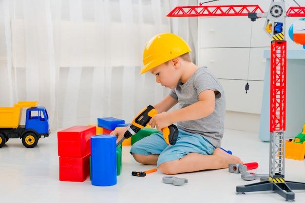 Kleines kind 4 jahre alt, spielt mit vielen bunten plastikspielzeugen im raum Premium Fotos