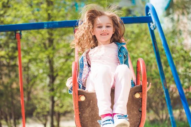 Kleines kind auf schaukel im park Premium Fotos