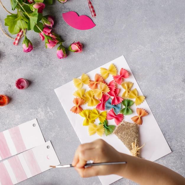 Kleines kind, das einen blumenstrauß aus farbigem papier und farbigen teigwaren heraus tut. Premium Fotos