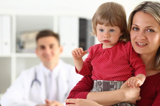 Kleines kind mit mutter am kinderarztempfang Premium Fotos