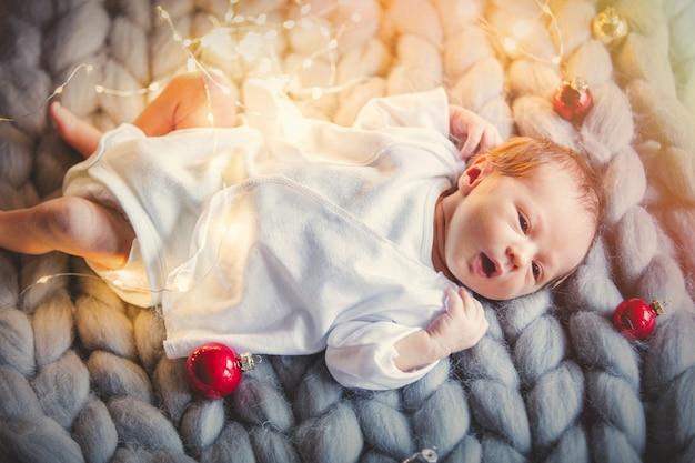 Kleines kind mit weihnachtskugeln herum Premium Fotos