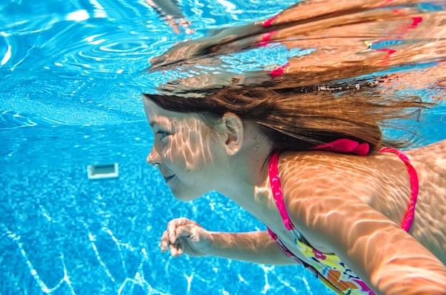 Kleines kind schwimmt unter wasser im schwimmbad, glückliches aktives baby taucht und hat spaß unter wasser Premium Fotos