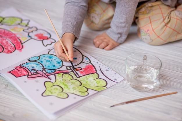 Kleines kind zeichnet wasser zu hause färben mit pinsel Premium Fotos