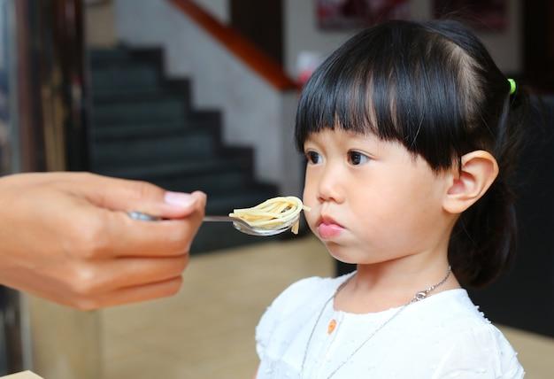 Kleines kindermädchen, das langweiliges lebensmittel isst. Premium Fotos