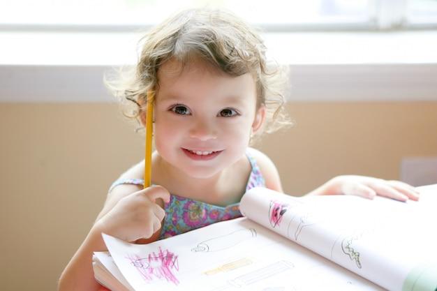 Kleines kleinkindmädchen, das in der schule schreibtisch schreibt Premium Fotos
