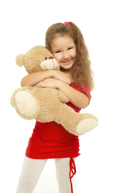 Kleines lächelndes mädchen umarmt mit bären im roten kleid, das auf weiß lokalisiert wird Kostenlose Fotos
