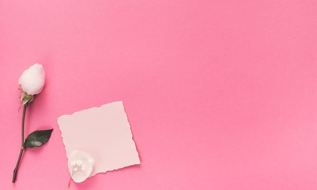 Kleines leeres papier mit weißer blume auf rosa tabelle Kostenlose Fotos