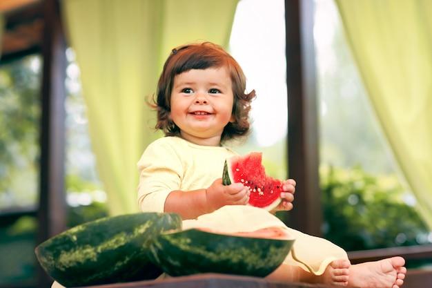 Kleines lockiges kleinkind isst eine saftige wassermelone im garten. kinder essen obst auf der straße. gesundes essen für kinder. gartenarbeit für kleinkinder. Premium Fotos