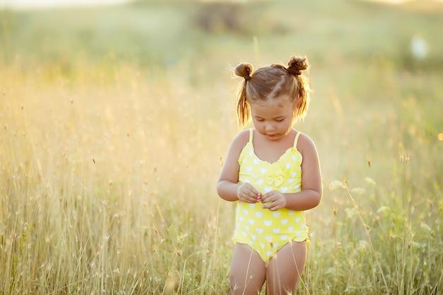Kleines mädchen 3-5 jahre alt im sommer auf dem feld mit gelben ährchen in einem gelben badeanzug. Premium Fotos