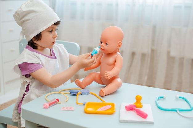 Kleines mädchen 3 jahre alte vorschüler, die doktor mit puppe spielen. das kind macht ein injektionsspielzeug. Premium Fotos