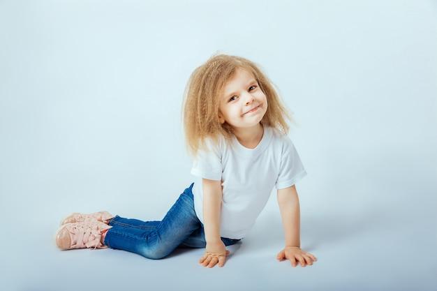 Kleines mädchen 4 jahre alt mit tragendem weißem hemd des gelockten haares, blue jeans, rosa stiefeln, die auf dem boden sitzen, lächeln und schauen Premium Fotos