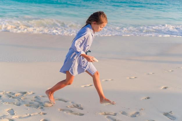 Kleines mädchen am weißen strand bei sonnenuntergang Premium Fotos