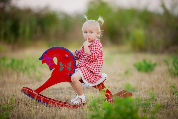 Kleines mädchen auf einem spielzeugpferd spazieren im sommer Premium Fotos